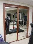 фото двойные раздвижные межкомнатные зеркальные двери в деревянном обрамлении